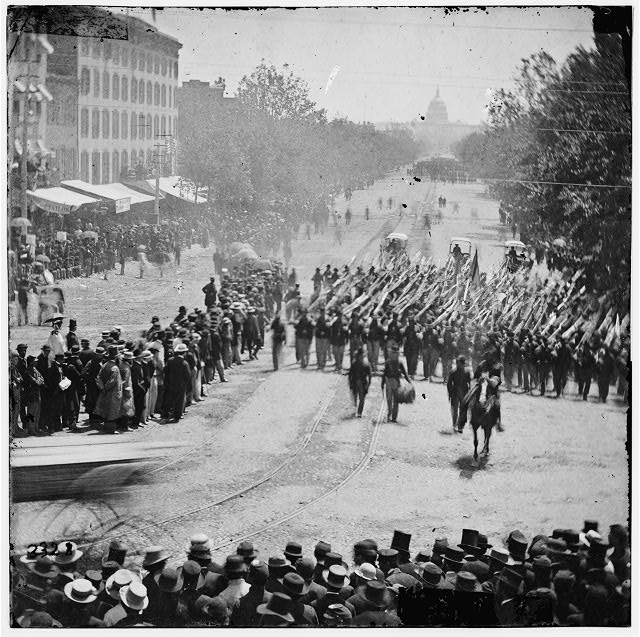 [Washington, D.C. Infantry unit with fixed bayonets followed by ambulances passing on Pennsylvania Avenue near the Treasury]