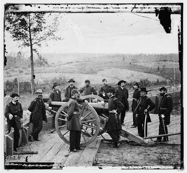 [Atlanta, Ga. Gen. William T. Sherman, leaning on breach of gun, and staff at Federal Fort No. 7]