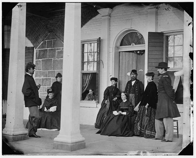 [Fort Monroe, Va. Officers and ladies on porch of a garrison house]