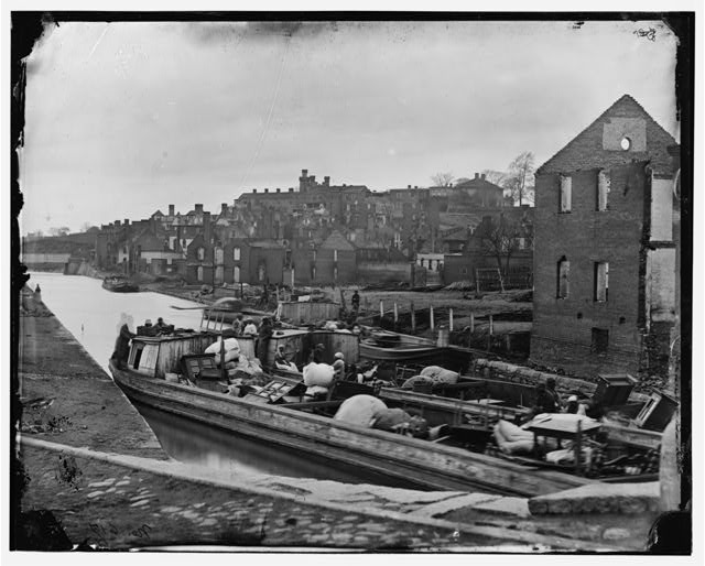 [Richmond, Va. Barges with African Americans on the Canal; ruined buildings beyond]