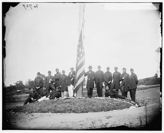 [Washington, D.C. Signal Corps officers lowering flag at their camp near Georgetown; Gen Albert J. Myer, in civilian dress, at right of pole]
