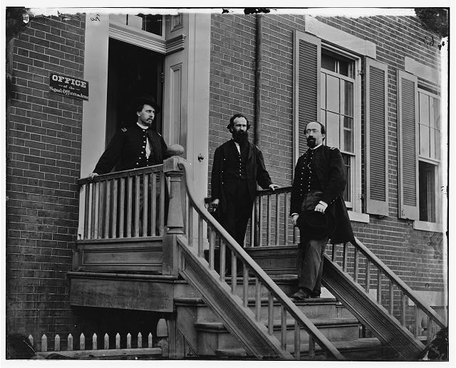 [Washington, D.C. Col. Benjamin F. Fisher between two officers on steps of Signal Corps headquarters, 1816 F St., NW Avenue at Madison Place NW]