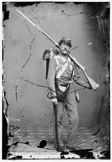 [Unknown location. Unidentified Union volunteer with shouldered rifle and bayonet in photographer's studio]
