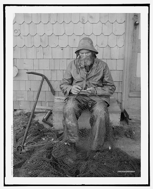 A Cape Ann fisherman mending his nets