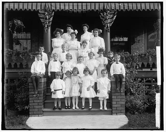 [Children and women on steps of house, possibly school children and teachers]
