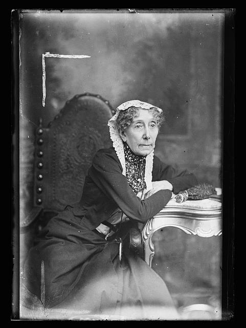 [Elderly woman in lace cap leaning on table, three-quarter-length portrait]