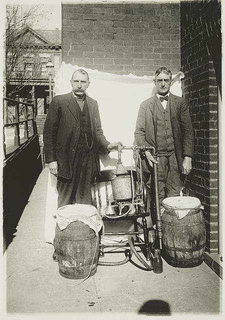 [Two men posing with a whiskey still]