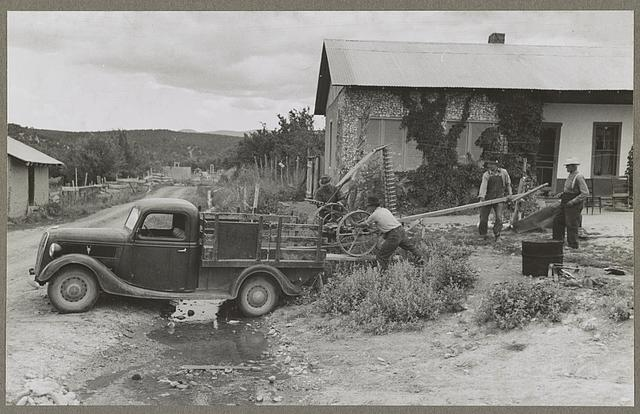 Chamisal, New Mexico. Spanish-American farmers loading a mower onto a truck