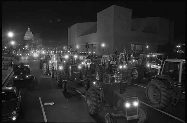 [Farmers driving tractors at night on Pennsylvania Avenue, as part of an American Agriculture Movement rally, Capitol dome in background, Washington, D.C.]