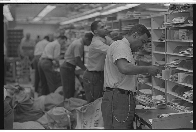 [African American postal employees sorting mail into cubbyholes]