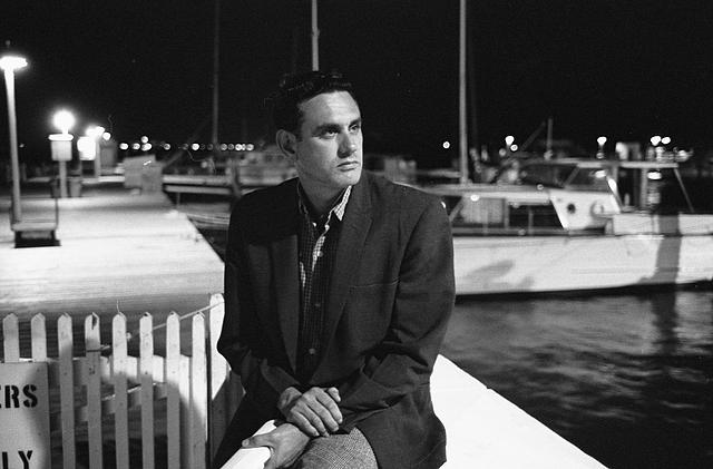 "[Tony Cuesta, military leader of the anti-Castro group Commandos L, who led a raid on the Russian ship ""Baku"", seated at pier with boats behind him, Miami, Florida]"