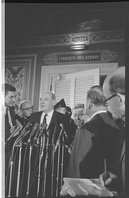[Secretary of State, Dean Rusk, standing behind microphones, at a meeting of the Senate Foreign Relations Committee]