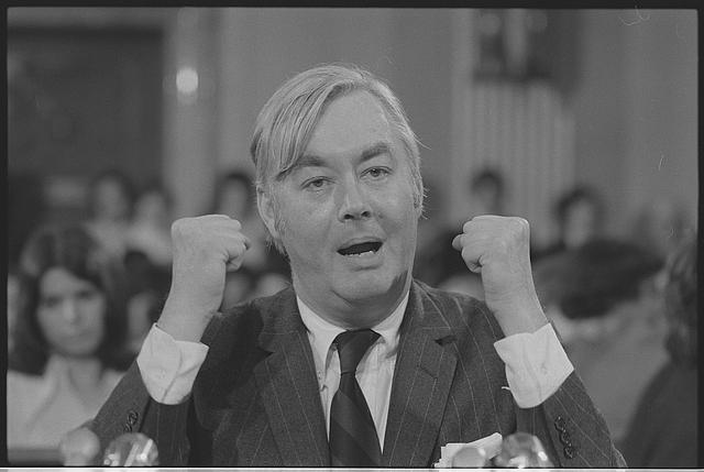 [Daniel Patrick Moynihan, head-and-shoulders portrait, speaking behind microphones, gesturing with his hands, probably at a meeting of the Senate Committee on Foreign Relations]