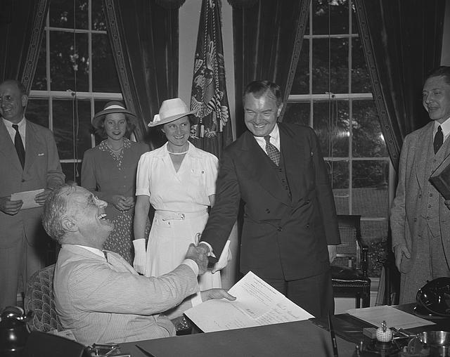 Robert Jackson sworn in as Justice. Washington,D.C. July 11 --Robert Jackson was sworn in as Associate Justice of the Supreme Court in President Roosevelt's office before an audience comprising most of the high officials of the New Deal with whom he had been associated for seven years. Picture shows the President as he congratulates Jackson. Left to right--Mary Jackson, daughter of Mr. Jackson, Mrs. Jackson and Robert Jackson. President Roosevelt is in left foreground