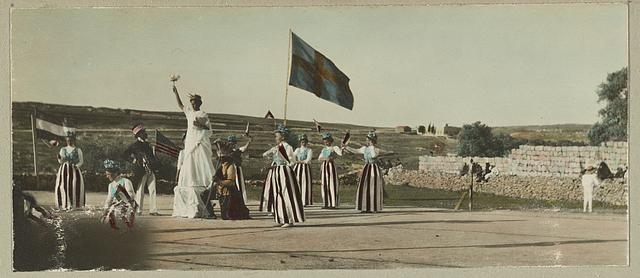 [Fourth of July pageant at the American Colony, Jerusalem, showing women wearing red, white, and blue costumes carrying flags and a man and woman dressed as Uncle Sam and the Statue of Liberty]
