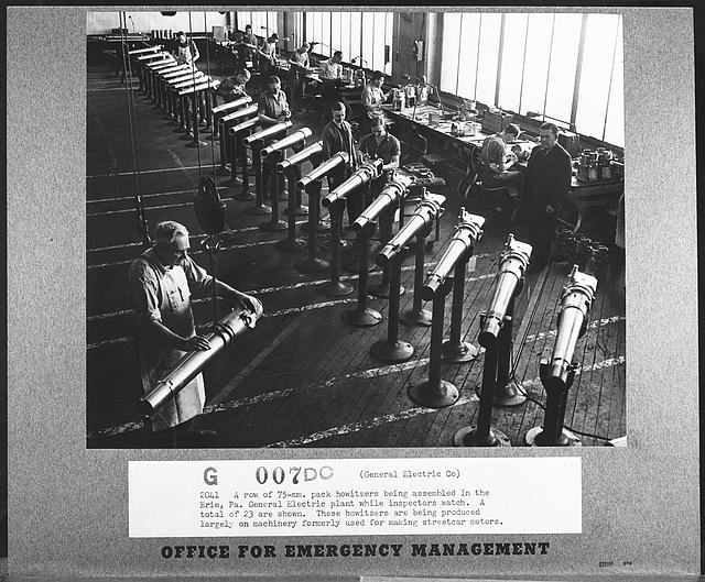 A row of seventy-five millimeter pack howitzers being assembled in the Erie, Pennsylvania, General Electric plant while inspectors watch. A total of twenty-three are shown. These howitzers are being produced largely on machinery formerly used for making streetcar motors