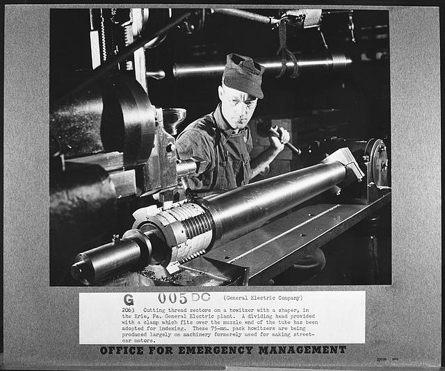 Cutting thread sectors on a howitzer with a shaper, in the Erie, Pennsylvania, General Electric plant. A dividing head provided with a clamp which fits over the muzzle end of the tube has been adopted for indexing. These seventy-five millimeter pack howitzers are being produced largely on machinery formerly used for making streetcar motors