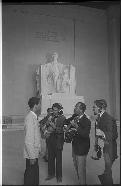 [Men playing guitars and singing at the Abraham Lincoln statute inside the Lincoln Memorial during the March on Washington, 1963]