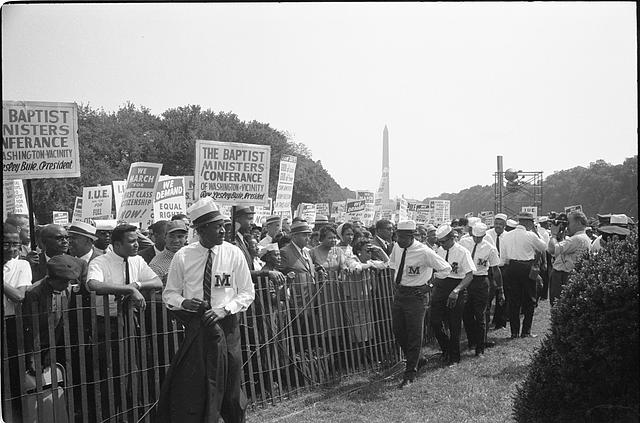 "[Marshals standing by fence near crowd carrying signs, including ""Baptist Ministers Conference of Washington & Vicinity"" and ""We March for First Class Citizenship Now,"" during the March on Washington, 1963]"