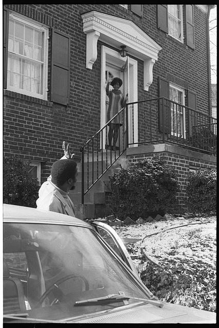 [African American man at his car, waving goodbye to family member who is in the doorway of a house in the suburbs]