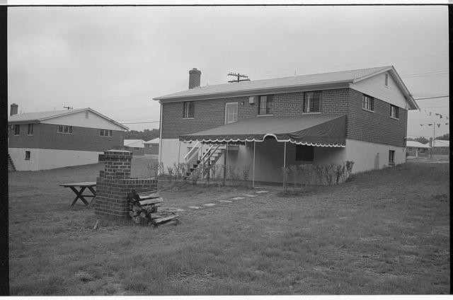 [Backyard of a brick house in the suburbs with picnic table and barbecue]