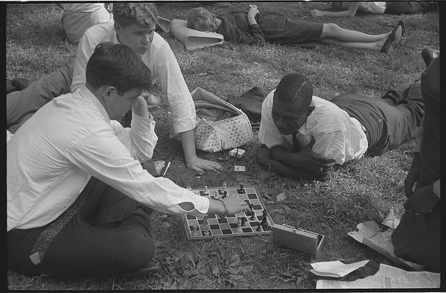 [Young men participants in the March on Washington playing chess on the grass]