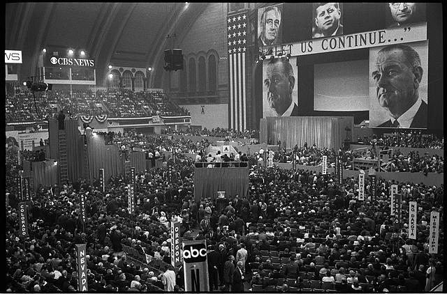 "[Aerial view of delegates and the stage with large pictures of John F. Kennedy, Harry Truman, Franklin D. Roosevelt, and Lyndon B. Johnson and the slogan ""Let us continue..."", at  the 1964 Democratic National Convention, Atlantic City, New Jersey]"