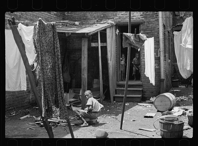 Negro backyard near Capitol, Washington, D.C. Negro children have just discovered the cameraman and are concerned at his presence