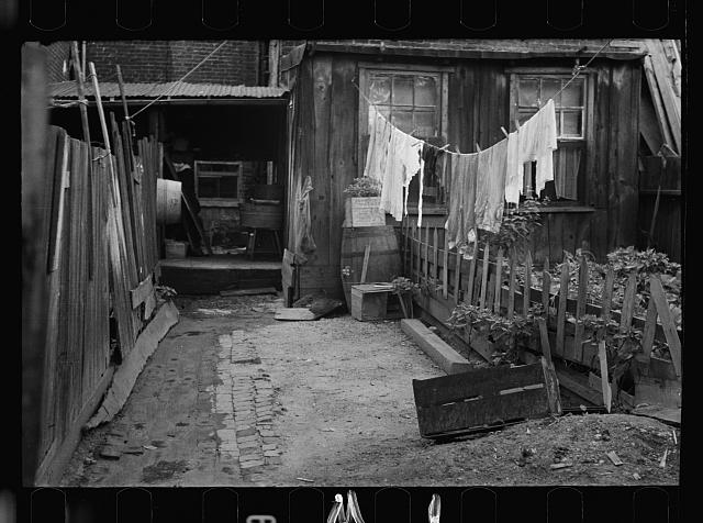 [Untitled photo, possibly related to: Front of Negro home near Capitol, Washington, D.C. Interiors of these homes vary little. A chair or two and a table, a bed and perhaps an extra mattress on the floor cares for six to ten people]