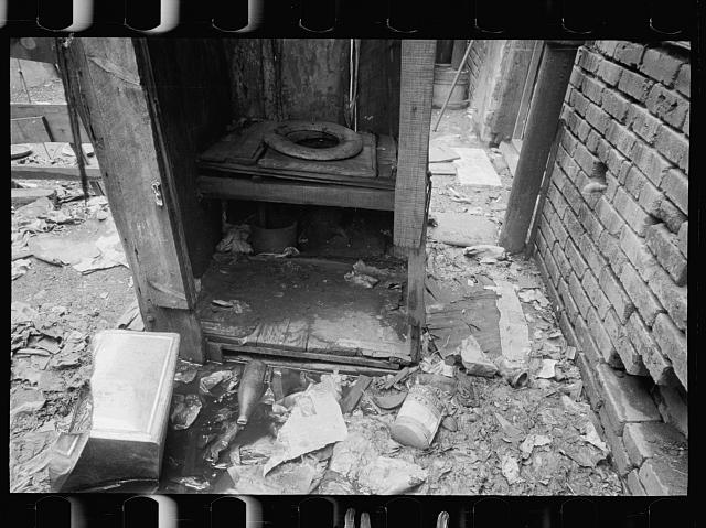 Privy near Capitol, Washington, D.C. This outbuilding leaks and drains on land about it. Negro inhabitants appear oblivious to it all. No door to this privy, but a sheet of canvas which is seldom used