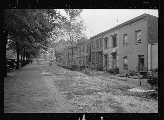 Section of Massachusetts Avenue showing block of shabby houses with outside toilets and water supply, Washington, D.C.
