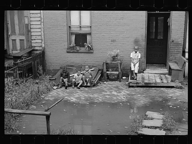 Front of old brick structure in section near Union Station, Washington, D.C. Land is low here and water collects in front and backyard after a rain and remains for many days. Entrances to privies are usually under water.  Interior of homes similar in shabbiness to exterior