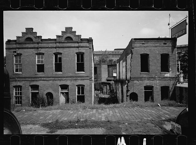 Ruins of old brick structures, Washington, D.C. Sections of these buildings are still inhabited. The Government Printing Office is shown in the background. This section of Washington has some of the worst housing conditions in the District and for the most part, is completely Negro.  None of these houses has inside toilets or water supply