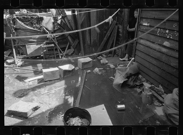 Negro backyard, Washington, D.C. Backyard near Stratford Hotel and within short distance from both the Capitol and Union Station, showing flooded yard and debris. In big rains, kitchen and bedroom floors of this house are so flooded that it is necessary to lay planks on them, the inhabitants say