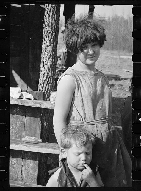 Twelve-year old girl of family of nine living in one-room hut built over the chassis of abandoned Ford truck in open field on U.S. Route 70 between Camden and Bruceton, Tennessee. Near backward Tennessee section. View also shows one of the small boys in family; the girl is dressed in a meal sack