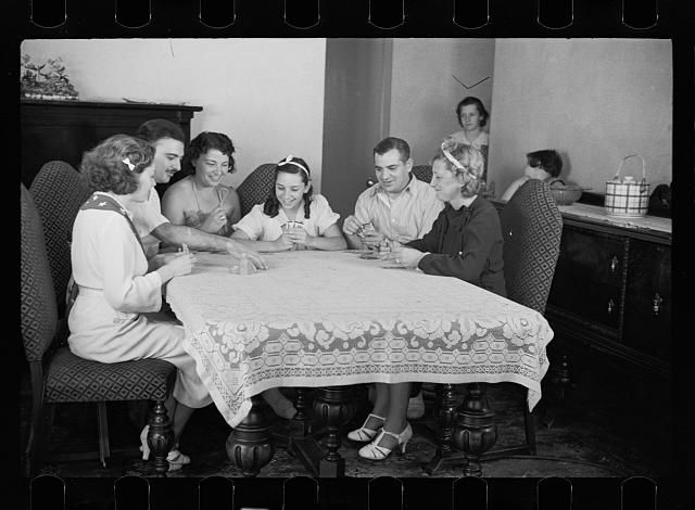 Family group playing cards in one of the new homes on the Hightstown Project, New Jersey