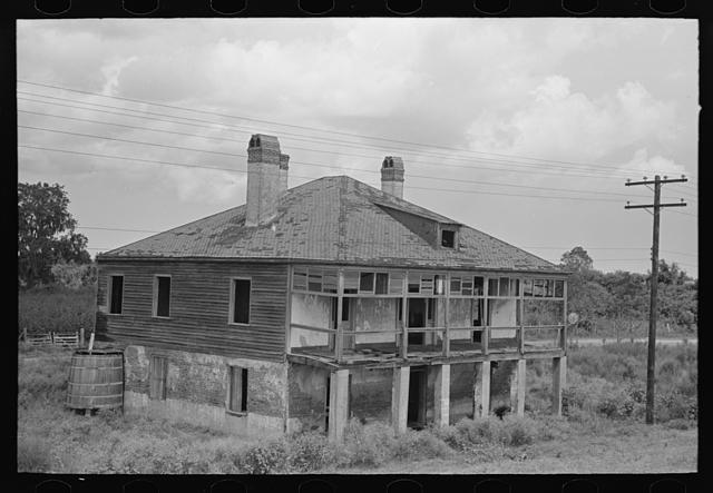 Abandoned plantation home, north of Destrehan, Louisiana. Lower floor is used as stable for cows; at present house is only few yards from levee, formerly was at least half a mile away