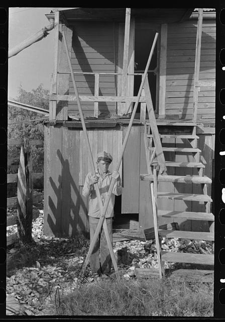 [Untitled photo, possibly related to: Boy with oyster rake used for scooping oysters in fishing operations, Olga, Louisiana]