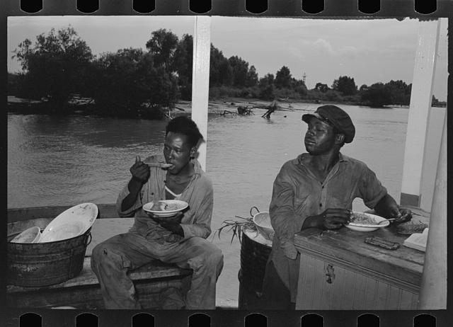 Negro stevedores eating on stern of boat. Food supplied to crew consists almost entirely of carbohydrates with some of the cheaper cuts of meat. Sleeping quarters are not provided for stevedores, who sleep in any available space. Aboard El Rito, Pilottown, Louisiana