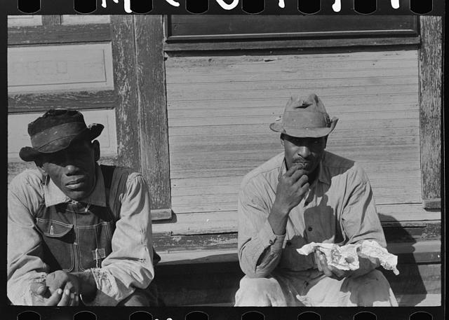 [Untitled photo, possibly related to: Negroes sitting on foot of the T&P (Texas and Pacific) railroad station, New Roads, Louisiana. Note frequency of train operations]