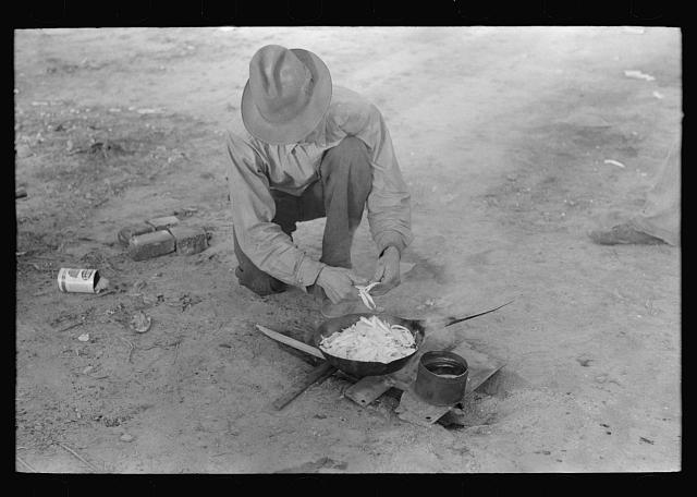 Migrant worker cooking meal over campfire, Edinburg, Texas. 1939