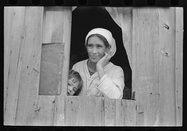 Mexican woman and son looking out of window into corral, San Antonio, Texas
