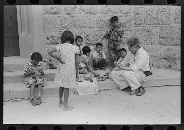 Tourist buying Indian pottery from children at Tesuque pueblo, New Mexico