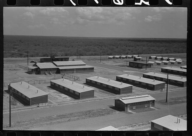 [Untitled photo, possibly related to: Row shelters in foreground, isolation units in right background, community house in left background, migratory labor camp, Sinton, Texas]