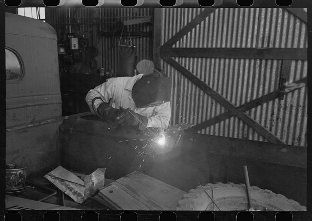 [Untitled photo, possibly related to: The United Producers and Consumers Cooperative maintains an automobile repair shop. In this picture, a worker is repairing a farmer's truck with an electric welder. Phoenix, Arizona]