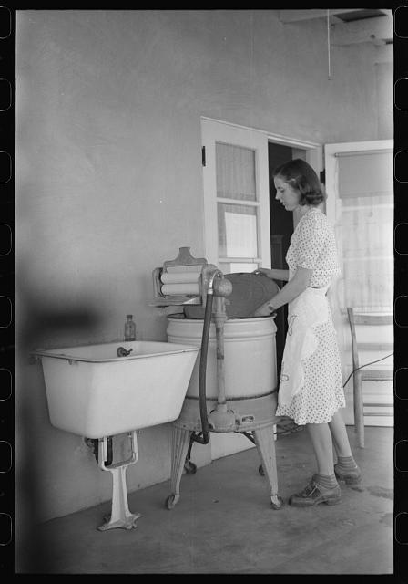 Woman living at the Casa Grande Valley Farms, Pinal County, Arizona, removing the cover from her electric washing machine