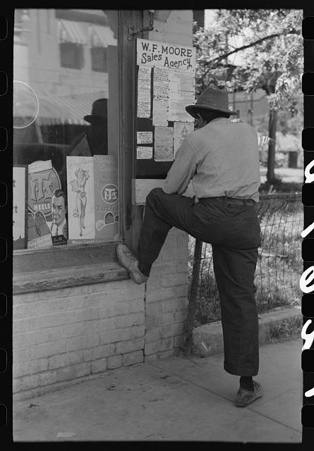 Man looking at sign on street of Silver City, New Mexico