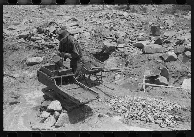 "Gold prospector pouring water into ""rocker,"" Pinos Altos, New Mexico"