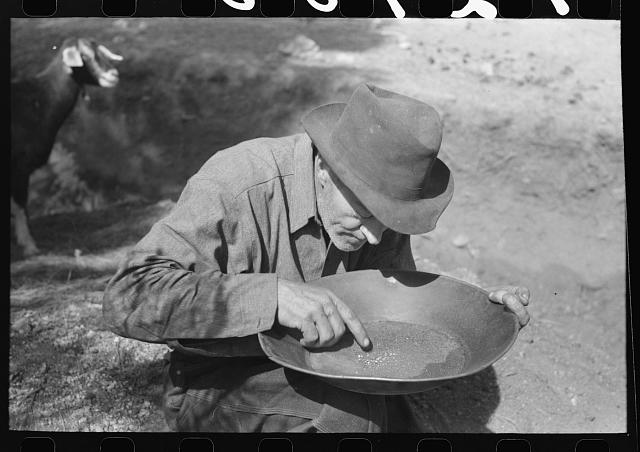 [Untitled photo, possibly related to: Prospector blowing on pan of fine dirt which contains particles of gold in order to blow the dirt away and leave the heavy gold. In this dry panning the pan is rotated until the dirt is on one side and then with a decisive toss it is thrown into the air, the light dirt being then blown away by the wind and the heavy gold being caught again in the pan. Pinos Altos, New Mexico]