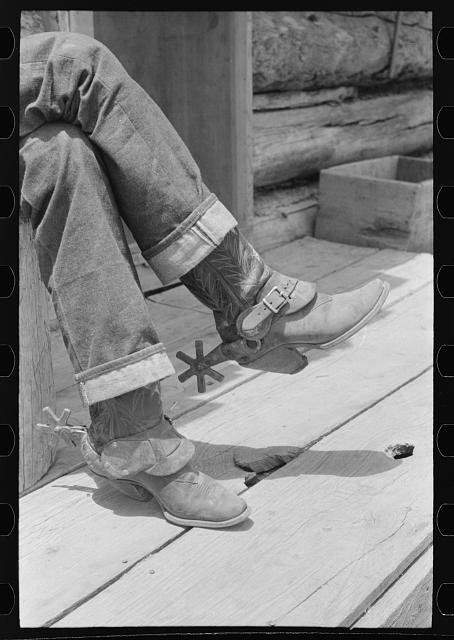 Detail of farmer's blue jeans, boots and spurs. This man was once a cowboy and still prefers the cowboy's dress. Pie Town, New Mexico.  Library of Congress.   Photographer:  Russell Lee.  1940.